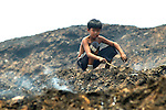 Although officially closed as a dump site for Manila, Smokey Mountain remains a resource for scavengers who tease items of value out of the still-smoking mound of garbage..
