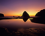 Southern Oregon Coastline with silhouetted rock formations dramatic sky at sunset with rock reflections in tidal pools, Whaleshead Beach along scenic corridor Oregon State USA