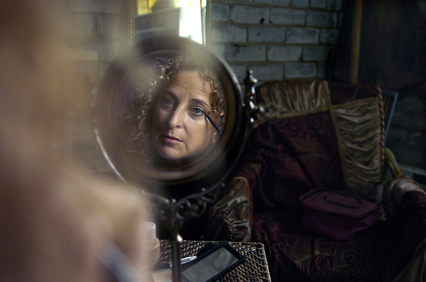 """Former Chicagoan and now resident of Three Oaks, Donna Blue Lachman applies makeup in her dressing room before performing her one act play, """"On Death and Gardening""""."""