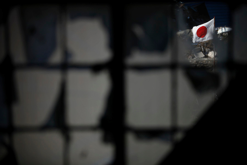 A Japanese flag is seen through the window of damaged house in Miyako, Iwate prefecture three weeks after the area was devastated by a magnitude 9.0 earthquake and tsunami April 1, 2011.   REUTERS/Damir Sagolj (JAPAN)