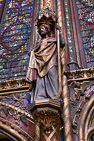 View from the side of pillar made of three small columns on each side of a larger central column decorated with golden Castilian castles and flanked by a statue of apostle, nave of the upper chapel of La Sainte-Chapelle (The Holy Chapel), 1248, Paris, France. La Sainte-Chapelle was commissioned by King Louis IX to house his collection of Passion Relics, including the Crown of Thorns. The Sainte-Chapelle is considered among the highest achievements of the Rayonnant period of Gothic architecture. Picture by Manuel Cohen
