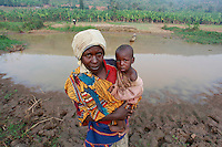 Clautilide Murekatete 40 and baby Aimee Iranzi aged 1 collecting drinking water from the Akagera river before farming her fields behind. Near Kajevuba Village. Juru Sector. Bugesera district. Rwanda...© Zute Lightfoot / Water Aid.