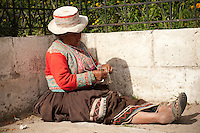 An older woman sits knitting in front of a church in the Colca Valley town of Lari. The women of the Colca Valley are skillful weavers and embroiderers. Female garments are worn with great pride, as each woven piece is a costly work of art.