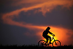 A cyclist pedals past the setting sun at the Chestnut Hill Reservoir on Thursday, July 21, 2011.