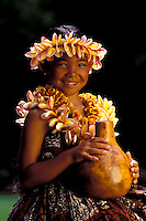 A young girl with a plumeria lei smiles while holding an ipu.