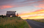 Idaho, North Central, Moscow. A barn and colorful sunset on a country road of the Palouse in Summer.