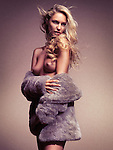 Beautiful half naked topless woman with long blond hair wearing a fur coat over nude body in golden colors