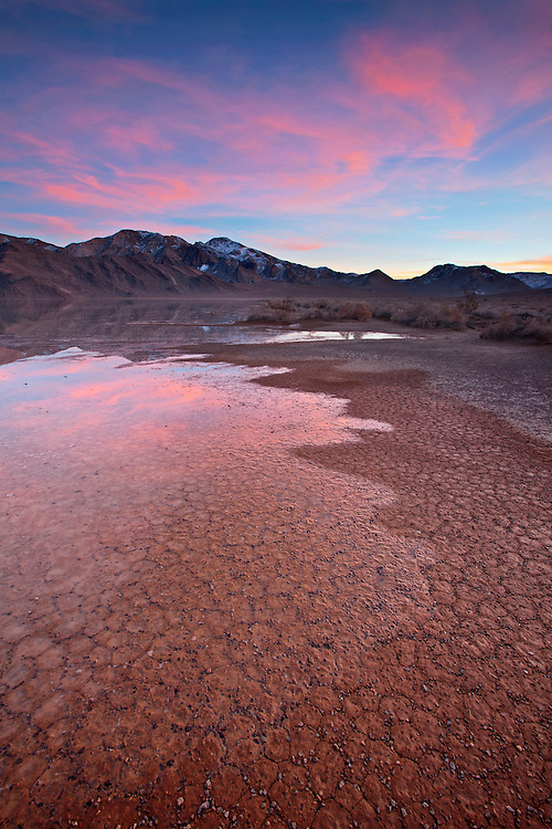 A colorful sunset erupts above the ice and water-filled Racetrack during winter in Death Valley National Park, California, USA