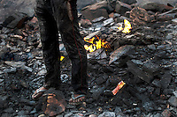 A man stands very close to a mine fire that has surfaced and, hence, all the more dangerous. A huge coal mine fire is engulfing the city of Jharia from all its sides. All scientific efforts have gone in vain to stop this raging fire. This fire is affecting lives of people living in and around Jharia. Jharkhand, India. Arindam Mukherjee.