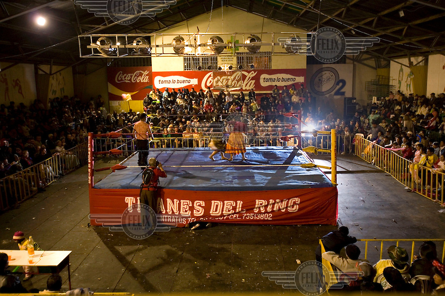 Two Cholitas fight at the Multifuncional building in El Alto. Cholitas are wrestlers of native Aymara descent and fight in traditional costume. Coca Cola advertisements line the walls..