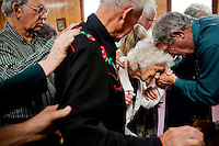"Mary Triplet receives anointment while surrounded by members of her congregation at church. Mary suffers from severe arthritis in her lower back making it extremely uncomfortable to sit through an entire sermon. A neighbor described the couple by saying, ""They are both just clinging to life becasue neither one wants to die and leave the other behind."""