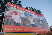 A billboard advertising 'original' phones. 'Clone' phones, frequently Chinese, copies of major brands, that resemble major brands at low prices are widely available in Uganda