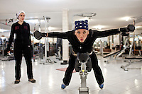 Two women weight training in a female only gym.