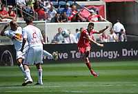Chicago midfielder Marco Pappa (16) shoots the ball in front of New York midfielders Joel Lindpere (20) and Teemu Tainio (2).  The Chicago Fire tied the New York Red Bulls 1-1 at Toyota Park in Bridgeview, IL on June 26, 2011.