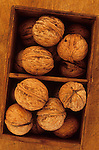 Close up from above of walnuts in their shells lying in compartmentalised wooden box