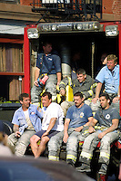 13 September 2001: NYC Fire crews rest on the back of a truck after the Terrorist attack on the America's.  Lower Manhattan, NY. Area surrounding ground zero where the World Trade Centers WTC once stood only hours after they fell to the ground in New York.  Islamic terrorist Osama bin Laden declares The Jihad or Holy War against The United States of America on September 11, 2001. Some of these workers will start suffering from a host of breathing and other health problems from responding to ground zero after trying to rescue victims.