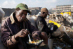 13 february 2013 - Dandora dumpsite, Nairobi, Kenya - A Kenyan man eats food waste that he found on the Kenya airways' trash at the Dandora dumpsite, one of the largest and most toxic in Africa. Located near slums in the east of the Kenyan capital Nairobi, the open dump site was created in 1975 and covers 30 acres. The site receives 2,000 tonnes of unfiltered garbage daily, including hazardous chemical and hospital wastes. It is a source of survival for many people living in the surrounding slums, however it also harms children and adults' health in the area and pollutes the Kenyan capital. Photo credit: Benedicte Desrus