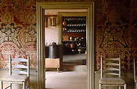 Boldly patterned wallpaper covers the walls of this room and a pair of chairs flanks the doorway leading to the kitchen and pantry