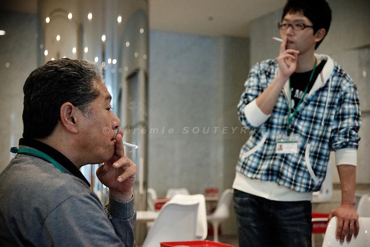 Tokyo, April 20 2011 - .(eng) Yuki Miyazawa and his father Yoshiyuki having a cigarette at the hotel lobby. Both of them took the decision for the family to leave Minami-Soma the day after he quake..(fr) Yuki Miyazawa et son pere Yoshiyuki fument une cigarette dans le hall de l'hotel. Les deux hommes de la famille ont pris tous les deux la decision de quitter la ville de MinamiSoma, le lendemain du seisme.