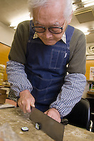 Chopping a plastic sushi roll using a real cooking cleaver at Maiduru Corporation, Tokyo, Japan, 22nd December 2008. Maiduru corporation makes highly realistic plastic food for display in restaurant and cafe windows. .