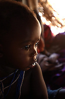 Yaeda Valley, Tanzania: Joyce Mahia, 7 months old, rests in her family's straw hut in a settlement of Hadzabe hunter gatherers in Northern Tanzania. The Hadzabe are one of the last tribes of practicing hunter gatherers in the world, and are on the verge of being pushed off their land by a company of United Arab Emirates princes who wish to use the area as their personal hunting ground. (PHOTO: MIGUEL JUAREZ LUGO)