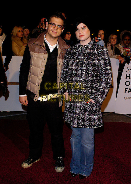 JACK & KELLY OSBOURNE.UK Music Hall Of Fame 2005 - live final, Alexandra Palace, London, UK..November 16th, 2005.Jack Osbourne and Kelly Osbourne.Ref: JH.full length brother sister family brown vest black white coat jacket hands in pockets.www.capitalpictures.com.sales@capitalpictures.com.© Capital Pictures.