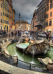 """The Colonna dell'Immaculata (""""Column of the Immaculate Conception"""") stands in in the piazza beyond the Fontana della Barcaccia (""""Fountain of the Old Boat"""") at the foot of the Spanish Steps in Rome, Italy.  (HDR image)"""
