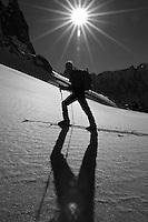 skier ascending under the sun