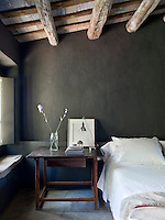 With its dramatic dark grey walls the master bedroom has been simply furnished and decorated