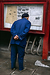 An elderly man reads a posting of the newspaper, China, 04/1989, Shanghai