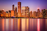 Photo of Chicago at night downtown city lakefront with John Hancock Building and other popular Chicago office buildings and skyscrapers.