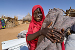 An internally displaced woman receives a blanket and other supplies at a distribution point in a camp in Darfur. The supplies were provided by the United Methodist Committee on Relief.