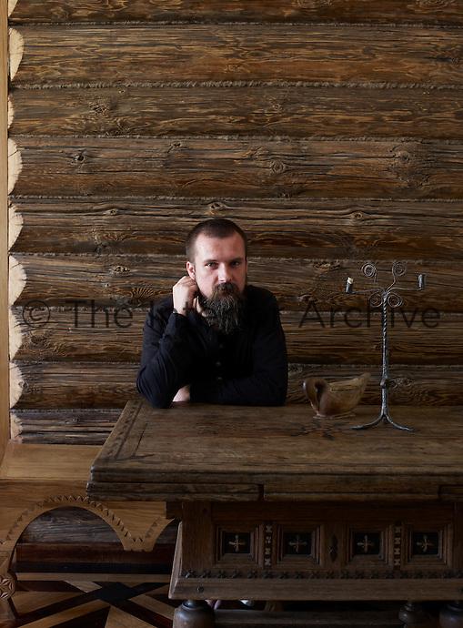 Antique dealer Denis Perestoronin in the living room of his Moscow apartment