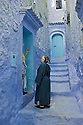 Women, wearing blue, stand in the doorway of their homes in a narrow blue alleyway in the city of Chaouen, Morocco.