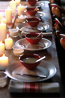 A candlelit table laid with red and white napkins and a combination of red and white crockery