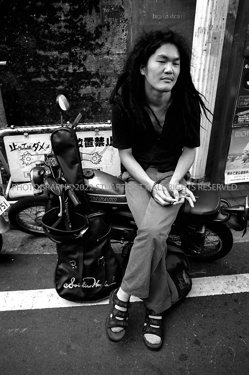"""8/10/2002--Shimokitazawa, Tokyo, Japan..A musician sits on his motorcyle as he waits for band mates outside a club...Wedged between Tokyo's Shinjuku and Shibuya wards, Shimokitazawa's maze of narrow streets form the ramparts of all that is non-conformist in get-along, go-along Japan. In """"Shimokita,"""" old village shops trade happily beside newer, eccentric clothing stores, funky restaurants, matchbox playhouses and live-music clubs. The unpretentious ambience is a magnet for students and other young visitors for whom Tokyo's usual street fashion scene has become more fascist than fun and mainstream entertainment is, well, too mainstream. Musicians, designers, aspiring actors and other would-be iconoclasts have settled the area, as have young professionals opting for a less-structured lifestyle. ...All photographs ©2003 Stuart Isett.All rights reserved.This image may not be reproduced without expressed written permission from Stuart Isett."""