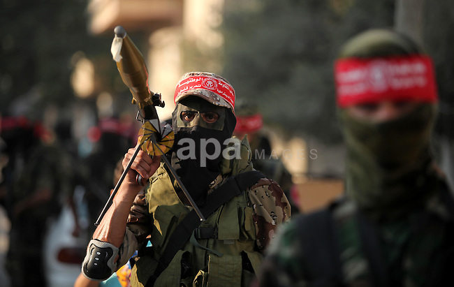 Masked Palestinian militants of the National Resistance Brigades, a group linked to the Democratic Front for the Liberation of Palestine hold their weapons during a military parade against the killing of a 18-month-old Palestinian toddler Ali Dawabsheh in Duma village, in Gaza city on July 31, 2015. The Palestinian toddler was burned to death and four family members injured in the arson attack on two homes in the occupied West Bank. Photo by Ashraf Amra