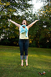Young brunette woman jumps for joy, her arms out stretched, on a tree lined grass lawn