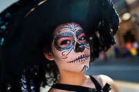 A young girl, dressed as 'La Catrina', a Mexican pop culture icon representing the Death, walks through the town during the Day of the Dead celebration in Morelia, Michoacán, Mexico, 1 November 2014. Day of the Dead ('Día de Muertos') is a syncretic religious holiday, celebrated throughout Mexico, combining the death veneration rituals of the ancient Aztec culture with the Catholic practice. Based on the belief that the souls of the departed may come back to this world on that day, people gather on the gravesites praying, drinking and playing music, to joyfully remember friends or family members who have died and to support their souls on the spiritual journey.
