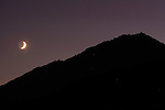 A crescent moon set behind Mount Tamalpais in Mill Valley, California.
