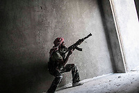 A rebel fighter belonging to the Kateba Omar Ben Abdul Aziz fires to the enemy position as he carries out a military operation to push back the Assad troops from the first line of fire in Aamria battlefield at the southwest of Aleppo City. .