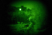 ARAB JABOUR, IRAQ - AUGUST 1: An American soldier watches a lone lit window in an extrememly rural town during a late night raid with Iraqi Sunni Concerned Citizens on August 1, 2007 in Arab Jabour, Iraq. Due to a high level of IEDs in the area the company size raiding party walked 5 kilometers to the target in complete darkness, raided the target houses, detained questionable suspects and walked 5 kilometers back to waiting humvees. (Photo by Benjamin Lowy/Reportage by Getty Images)(Photo by Benjamin Lowy/Reportage by Getty Images)