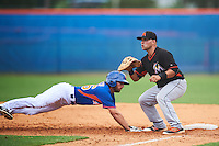 Miami Marlins first baseman Eric Gutierrez (20) waits for a throw as Gene Cone (76) dives back to first during an Instructional League game against the New York Mets on September 29, 2016 at the Port St. Lucie Training Complex in Port St. Lucie, Florida.  (Mike Janes/Four Seam Images)