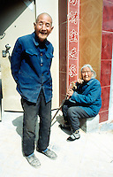 China. Province of Henan. Village Xiaotan. Portrait of a long lasting couple. The woman is hundred and one years old (101 - a century and a year) and the man 92 (ninety two). The husband and wife lived their entire life in the village. They stand in the sun near the entrance door to their house. © 2004 Didier Ruef