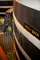 A well-worn step ladder next to an example of an antique wooden cask used in the distillation process