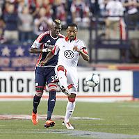 D.C. United defender James Riley (2) passes the ball as New England Revolution midfielder Saer Sene (39) closes. In a Major League Soccer (MLS) match, the New England Revolution (blue) defeated D.C. United (white), 2-1, at Gillette Stadium on September 21, 2013.