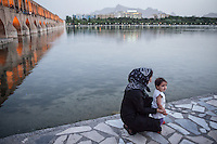 An Iranian mother and her daughter enjoy the early evening at Si-o-Seh Pol. Si-o-Seh Pol, a 298m long bridge with 33 arches, was built by Allahverdi Khan between 1599 to 1602 to link the two halves of Chahar Bagh street. It is also served as a dam, and still in use today to hold the water.