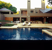 The vast outdoor living area of a house in Johannesburg viewed from across the swimming pool