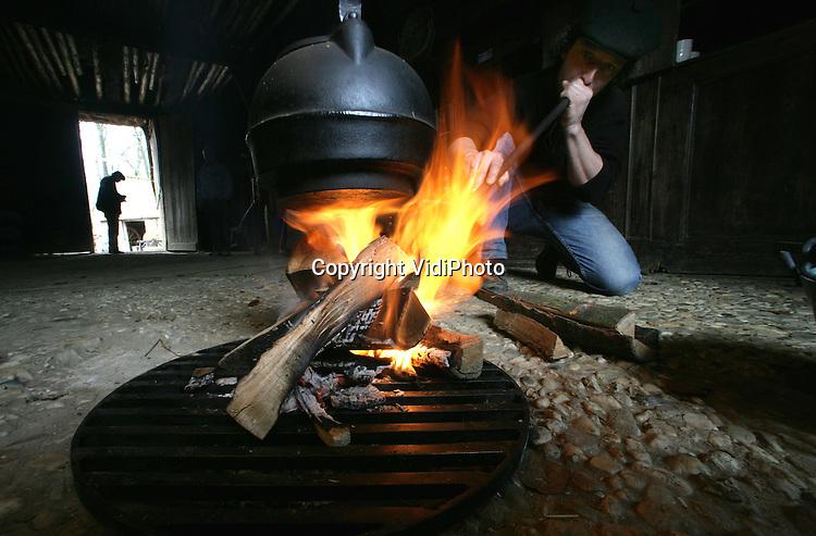 """Foto: VidiPhoto..ARNHEM - Een medewerker van het Nederlands Openluchtmuseum in Arnhem test vrijdag een open vuur in een van de historische boerderijen. Dit jaar wordt er in het Openluchtmuseum voor het eerst gekookt met open vuren in de oude boerderijen. In het """"los hoes"""" (foto) is geen schoorsteen, dus de rook trekt door het hele huis. Zaterdag opent het museum haar deuren voor publiek. Thema is dit jaar """"Eten en Drinken""""."""