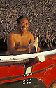 Lino Olopai, traditional sailing canoe navigator and Carolinian activist, with canoe; Saipan, Northern Marianas Islands.